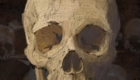 Human skull in foreground in thick paint. Skull and crossbones in background. Digital.